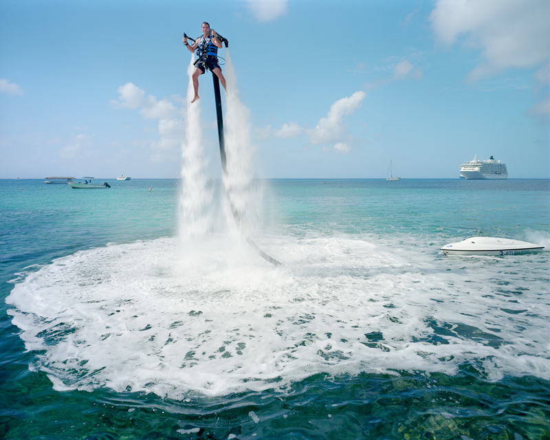 "An employee of ""Jetpack Cayman"" demonstrates this new watersport, now available on the island. Mike Thalasinos, the owner of the company, remarks, ""The Jetpack is zero gravity, the Cayman are zero taxes, we are in the right place!"" Grand Cayman © Paolo Woods e Gabriele Galimberti"
