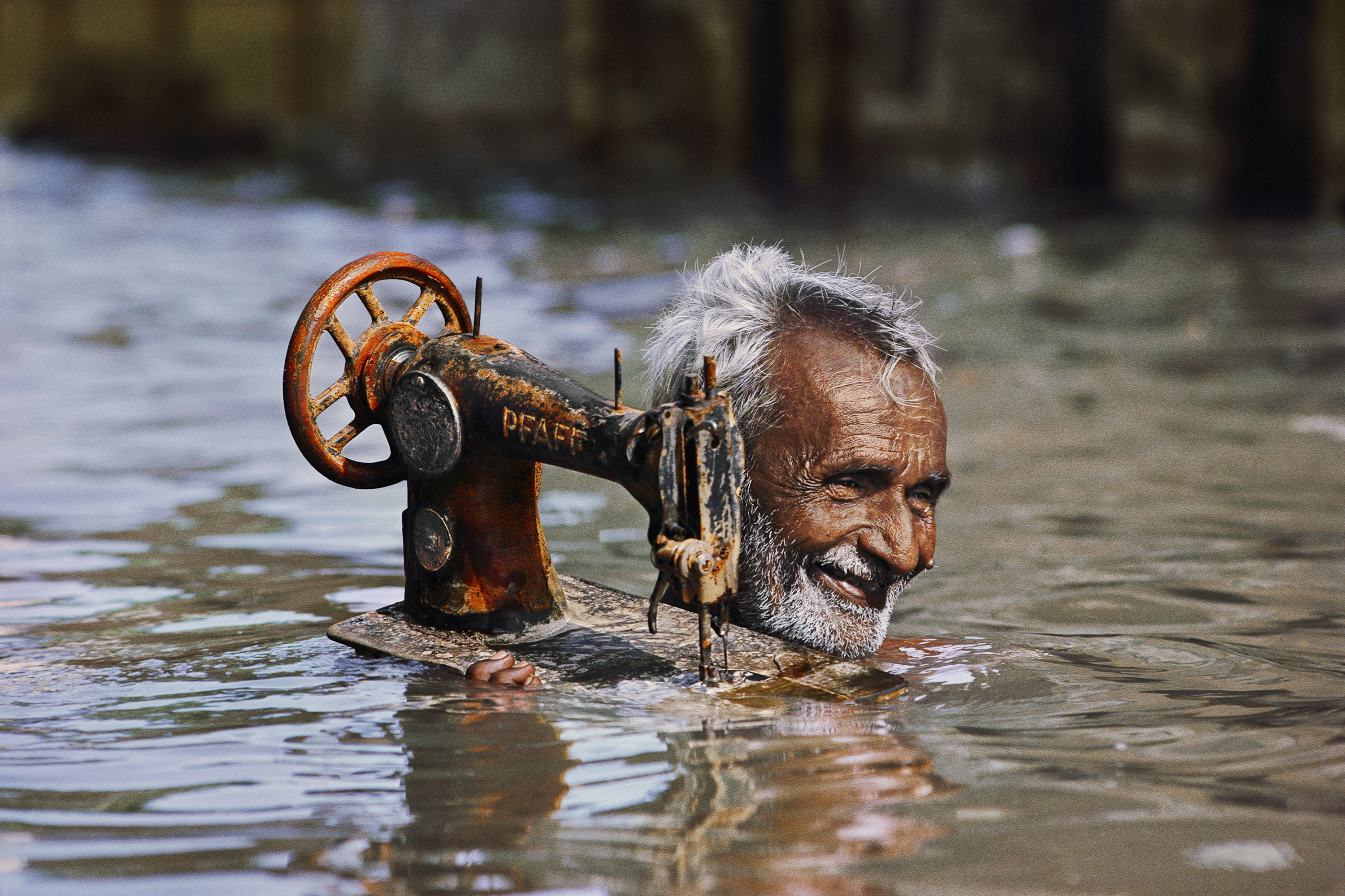 Tailor carries his sewing machine through monsoon floodwaters. Fonte: www.mucsarnok.hu